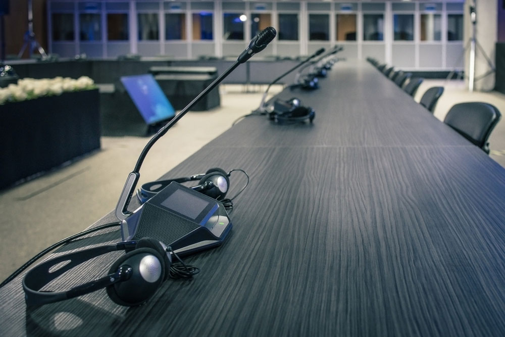 A row of headphones and microphones for translation during a meeting