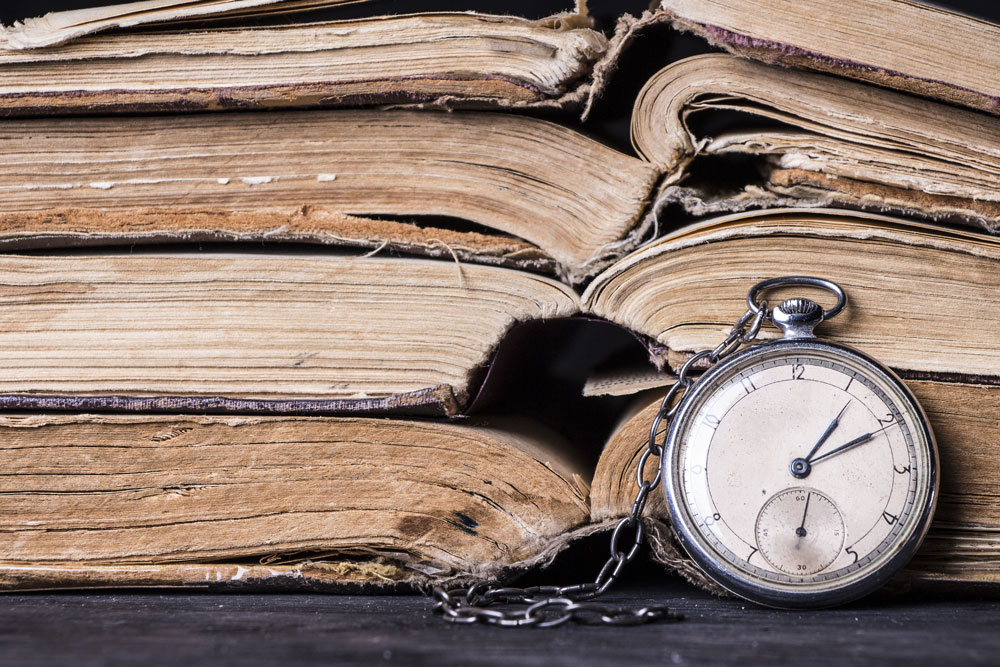 Open books stacked on top of each other with a pocket watch sitting in front of them