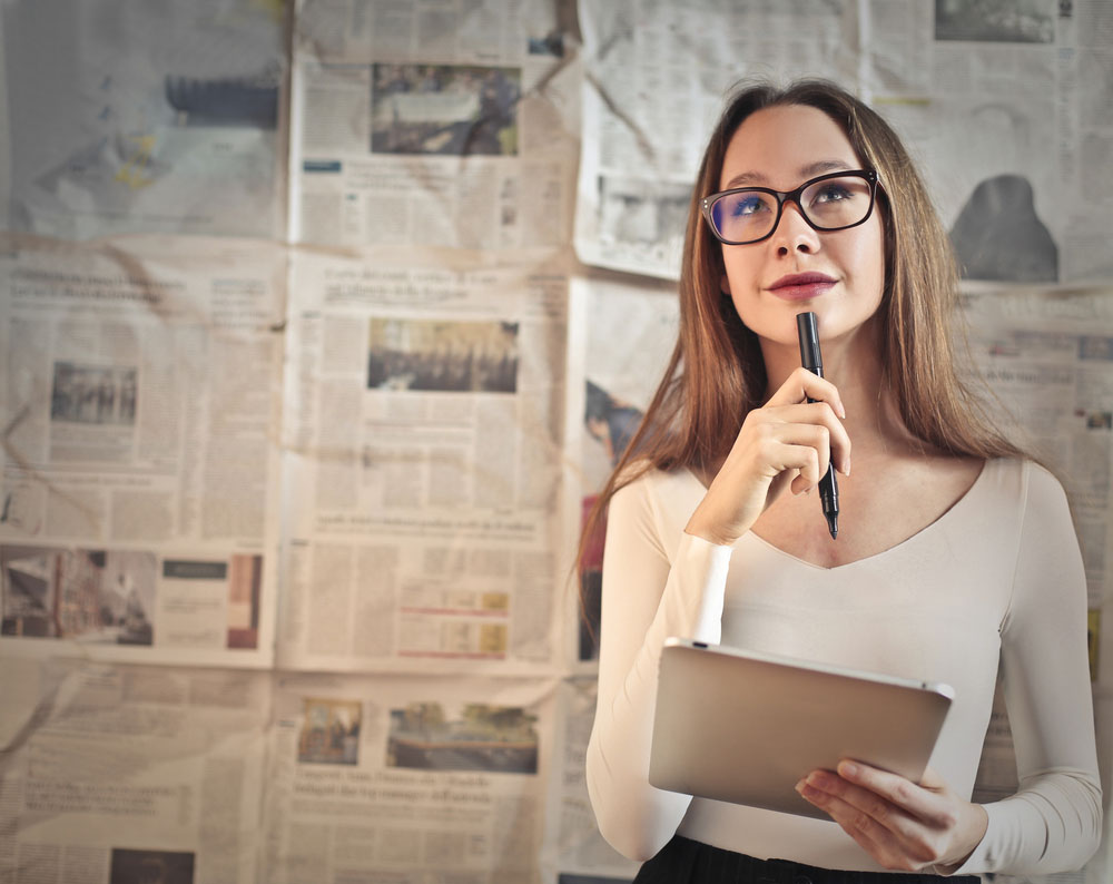 Woman standing in front of wall of newspaper clippings