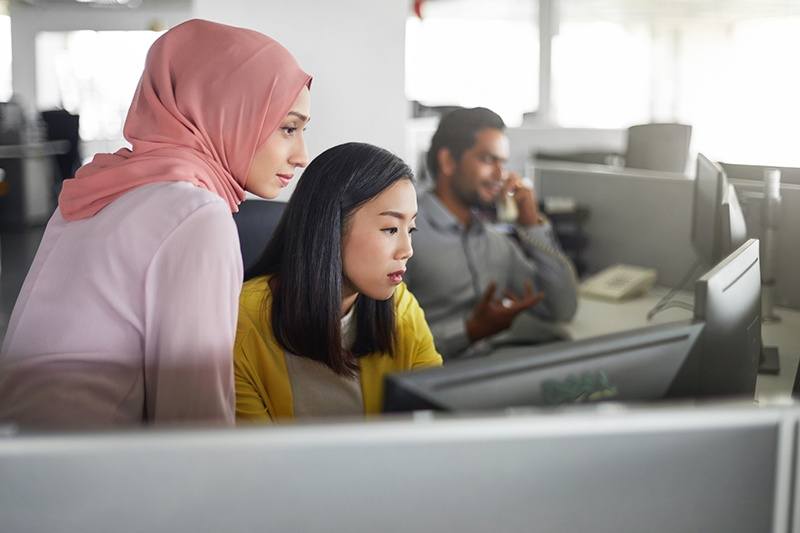Female-colleagues-working-at-computer-desk