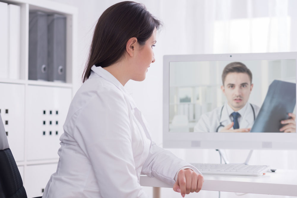 Two doctors talking to each other via video chat