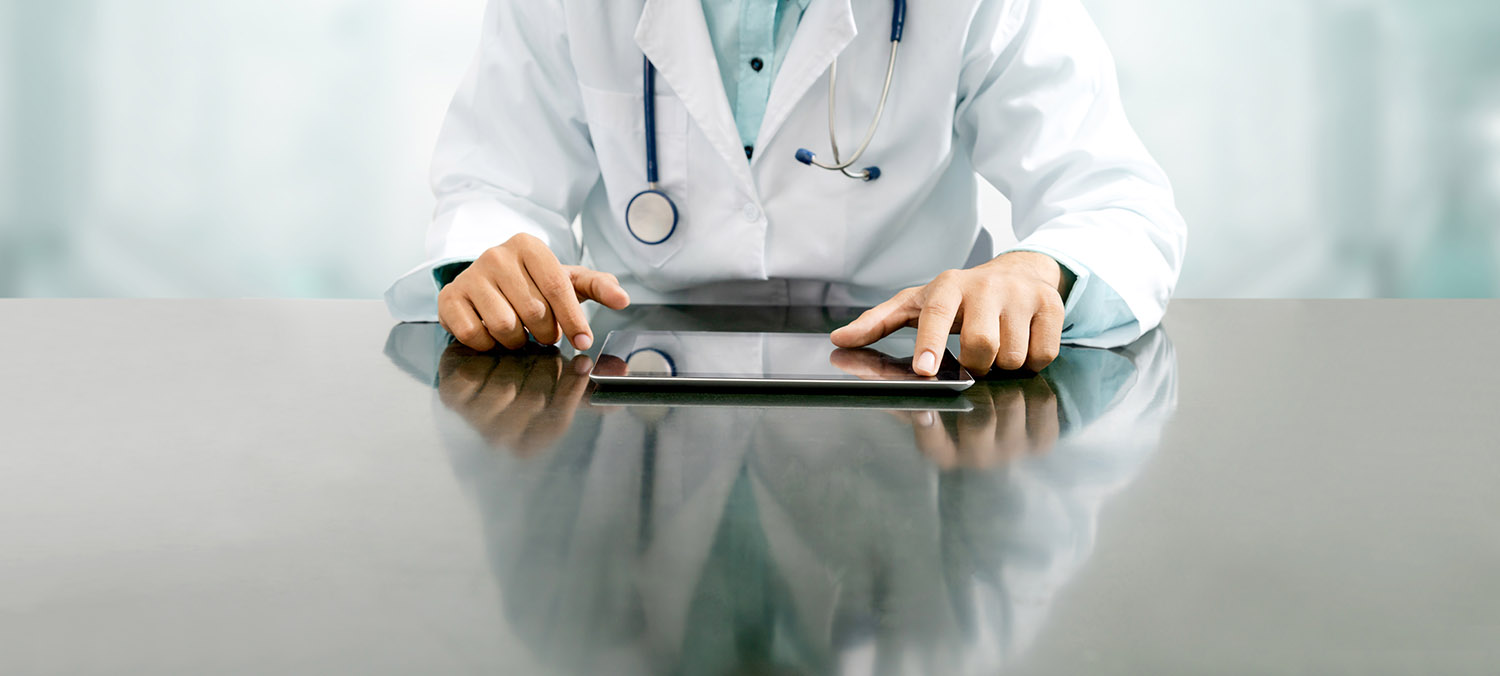 Healthcare Professional Using a Tablet Computer on a Table