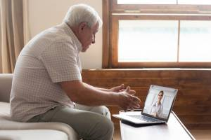 Older man using laptop for video call with a doctor