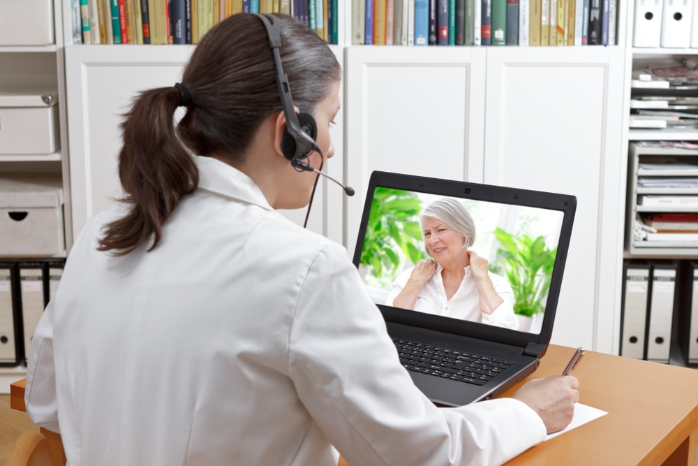 Woman with Headset Doing Telehealth Video Call with Older Woman