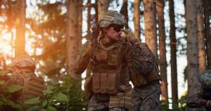Army men in forest using sign language