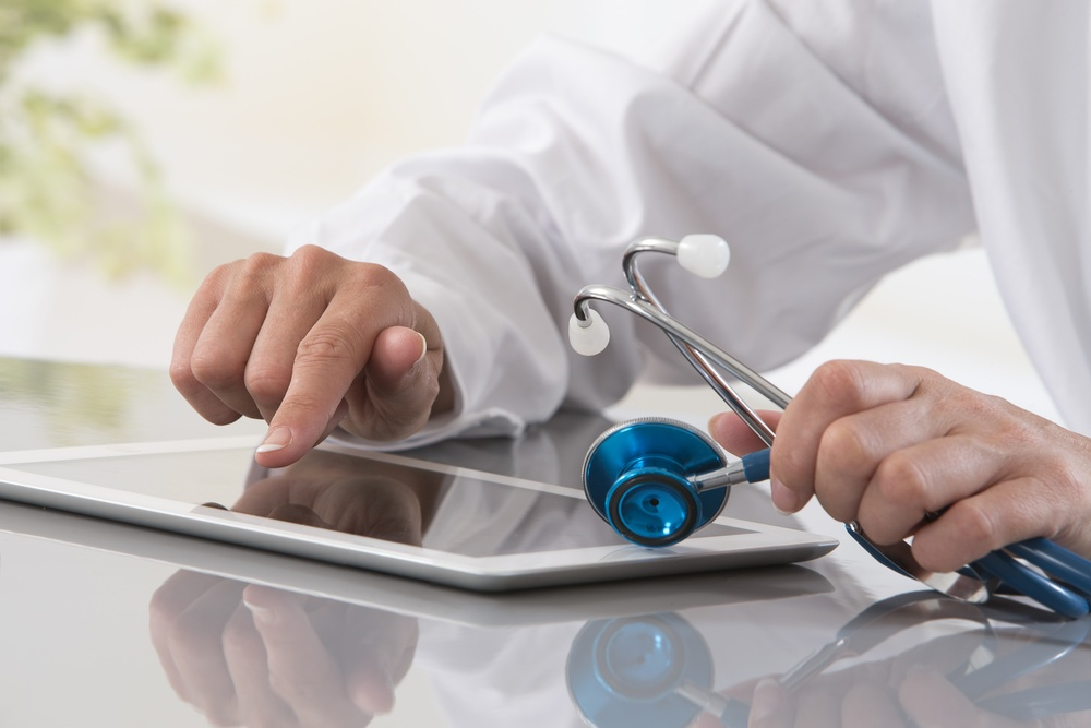 Doctor holding a stethoscope using a tablet computer