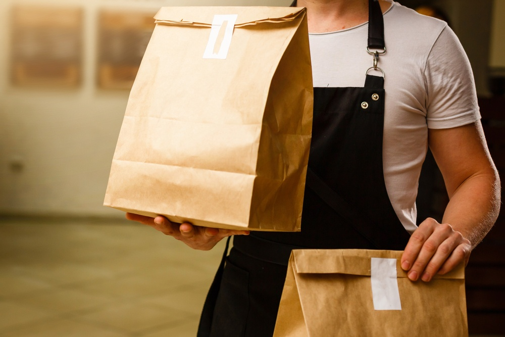 Man delivering two paper bags with food delivery