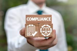 Image of a man in a white shirt with tie holding wooden blocks that say 'Compliance' in white writing and symbols