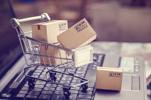 Image of a tiny shopping cart full of packages on a platform, symbolizing e-commerce