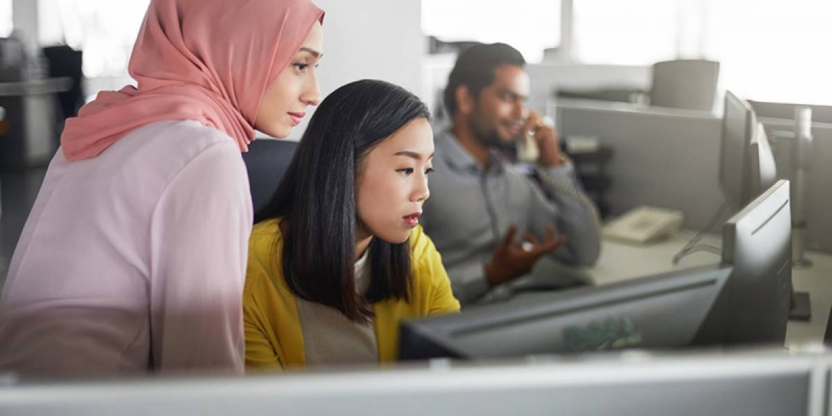 Businesswomen discussing over desktop PC in office. Female colleagues are looking in computer monitor. They are at workplace.