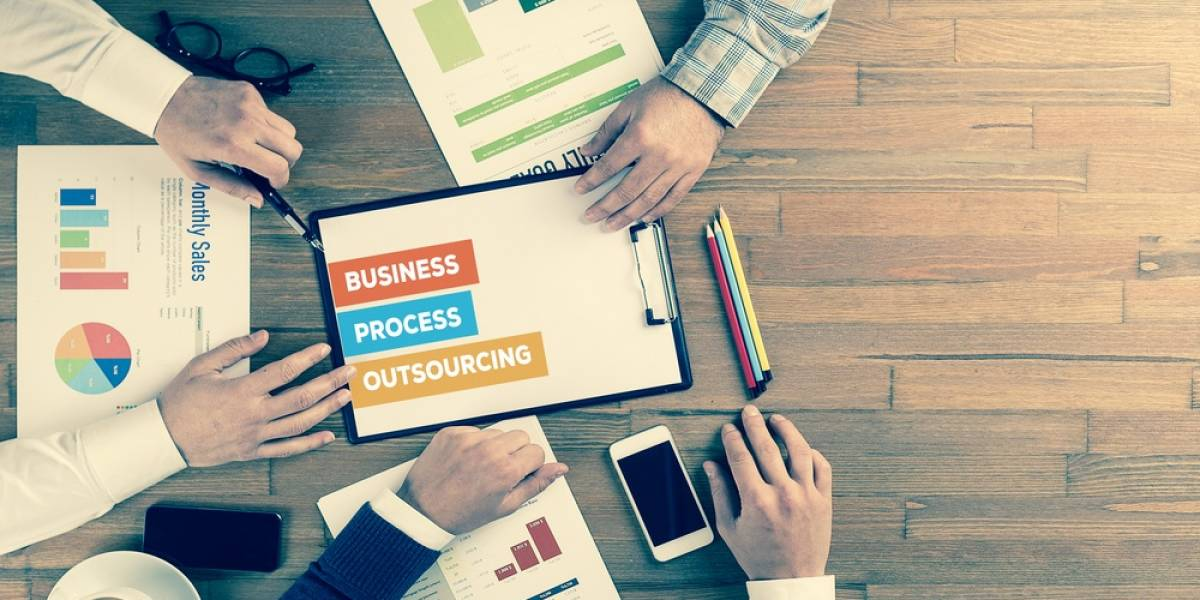 Image of multiple arms around a wooden table surrounded by papers with the words 'Business Process Outsourcing' in the middle