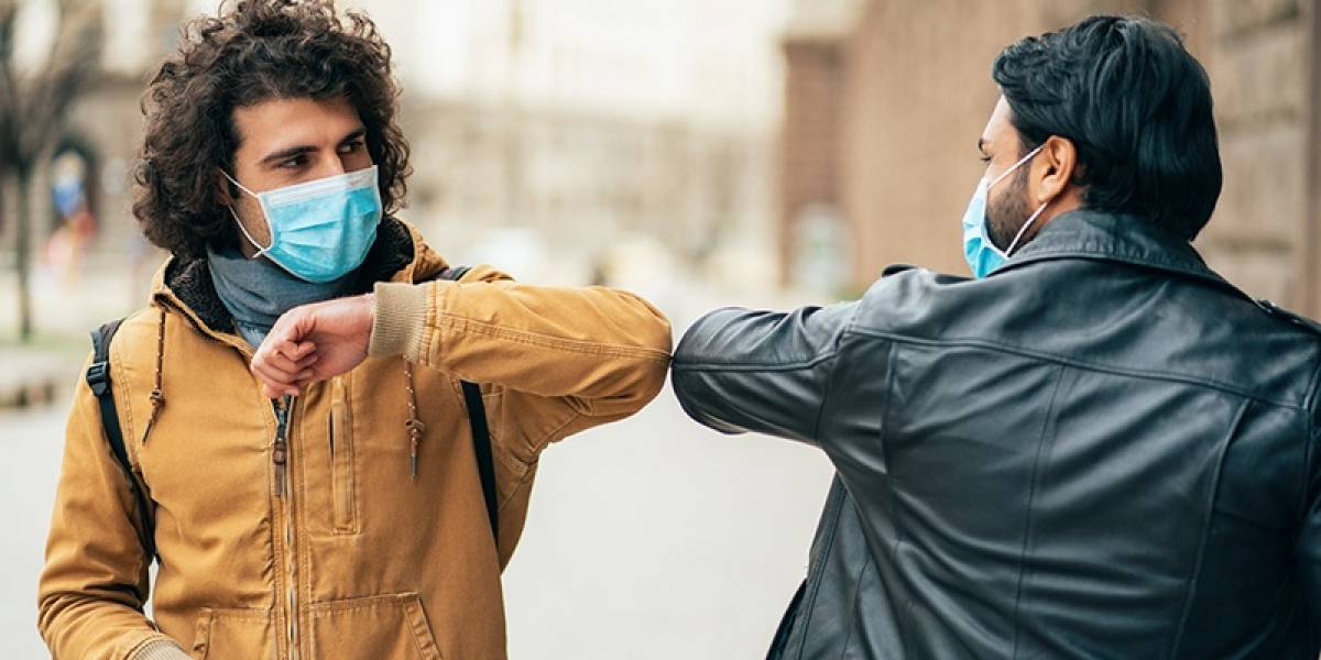 Young people friends meeting in quarantine and greeting without touching their hands