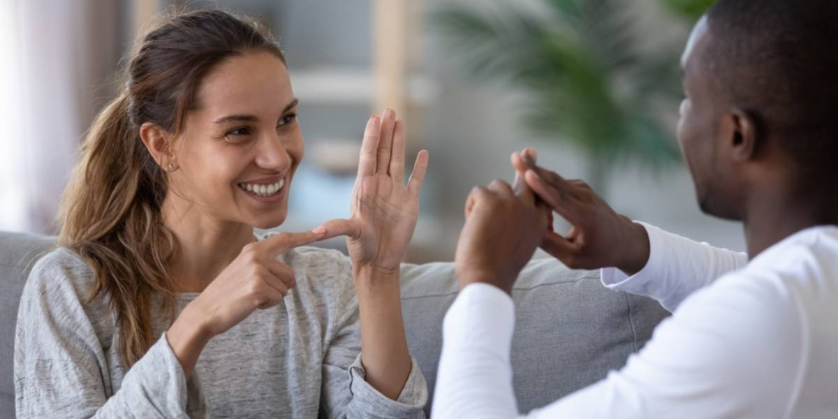 Smiling woman speaks sign language with a man
