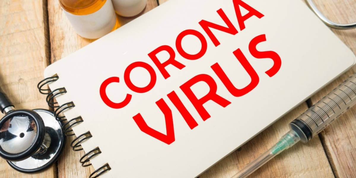 Notebook that Says Corona Virus Surrounded by Medicine and Syringe