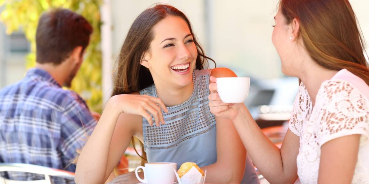 Young women drinking coffee and laughing