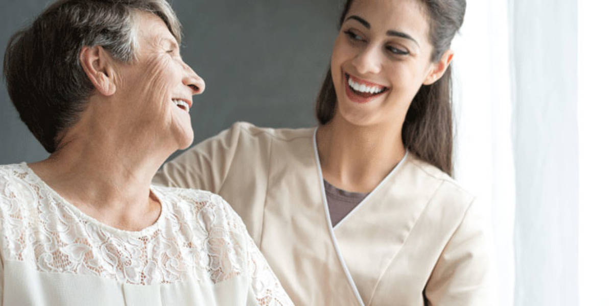 Older woman and nurse smiling at each other