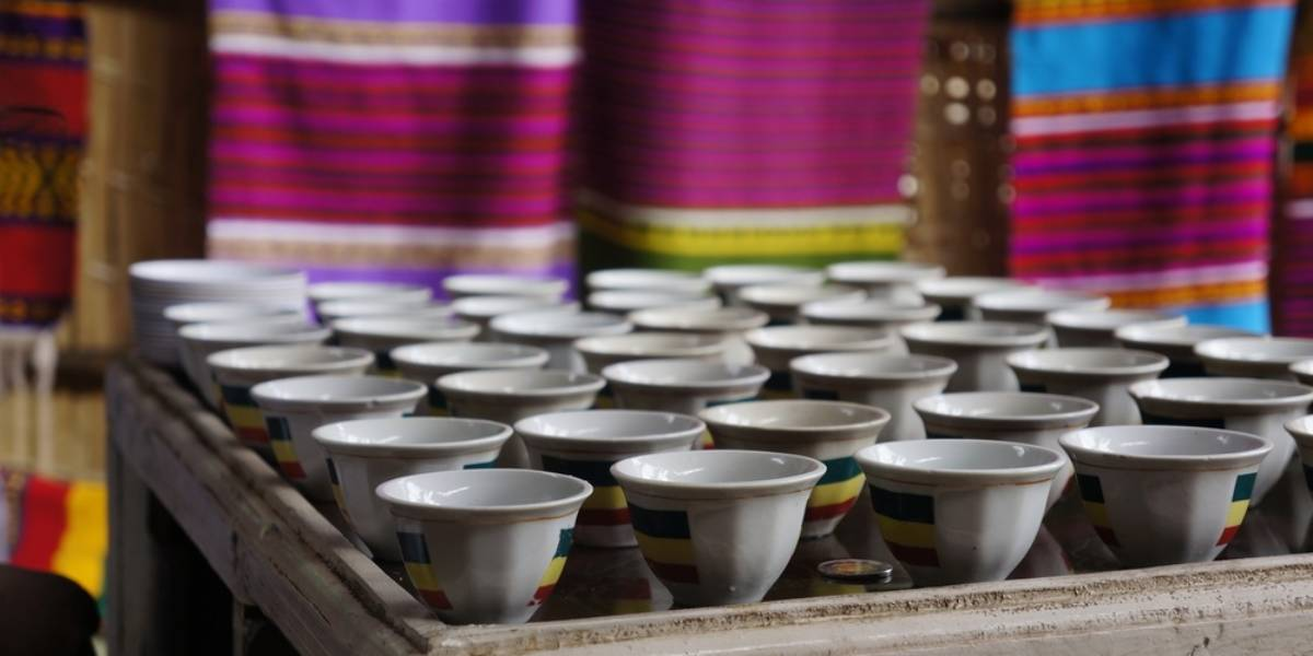 African tea cups on a tray in front of colorful cloths